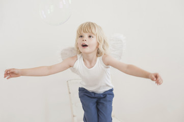 Kleiner Junge mit Flügeln und Seifenblase