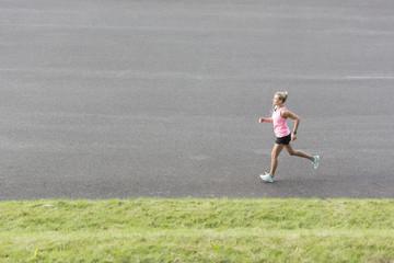 Polen, Warschau, junge Frau auf Asphalt laufend