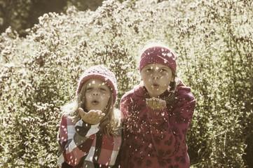 Zwei Mädchen pusten Samen