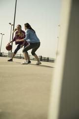 Zwei junge Frauen spielen Basketball im Freien