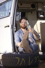 Man sitzt im Auto mit Reifen und Bierflasche