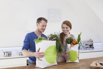 Paar mit Einkaufstaschen und Einkäufen