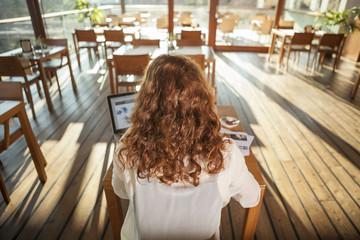 Junge Frau mit Notebook im Café