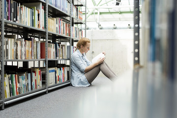 Student in einer Universitätsbibliothek sitzend auf dem Boden