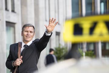 Deutschland, Berlin, Geschäftsmann ruft Taxi