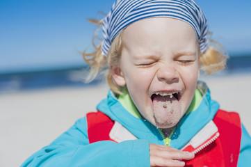 Deutschland, Mecklenburg-Vorpommern, Rügen, Junge mit Sand im Mund am Strand