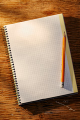 Open notebook on the table and pencil