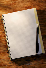Open notebook on the table and ballpoint pen