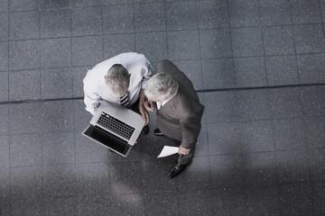Zwei Geschäftsleute mit Laptop im Büro, Lobby