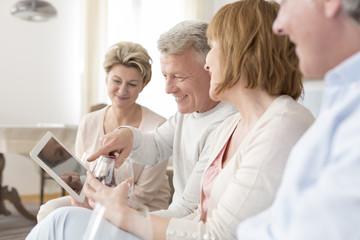 Zwei ältere Paare auf einer Couch im Wohnzimmer mit Tablet-Computer