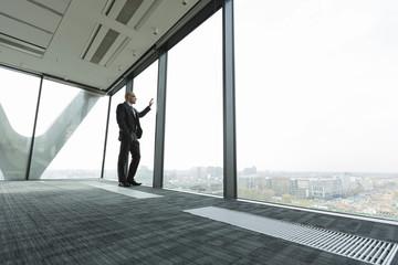 Geschäftsmann auf leerer Büroetage schaut aus dem Fenster