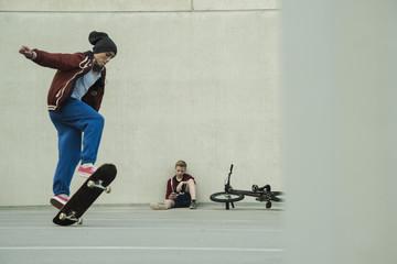 Zwei Jungen mit BMX-Rad und Skateboard auf Parkebene