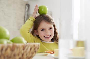 Deutschland, München, Mädchen sitzt am Tisch mit grünem Apfel