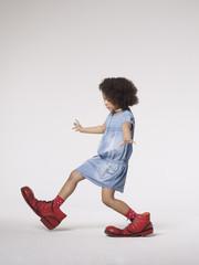 Mädchen, das in großen Clown-Schuhen steckt