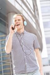 Glücklicher junger Mann mit Kopfhörern, Musik hören