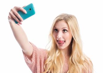 Mädchen macht Selfie und streckt Zunge heraus