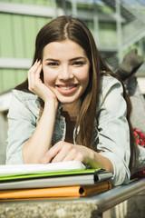 Lächelnde junge Frau Frau, brünett, liegt auf Bank