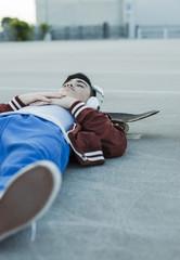 Junge mit Kopfhörern auf dem Boden liegend im Freien