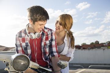 Glückliches Teenager-Paar im Freien auf Motorroller