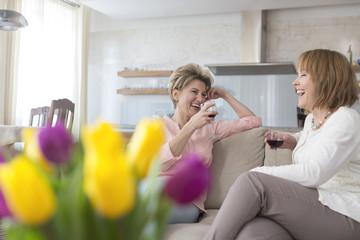 Zwei lachende reife Frauen trinken Rotwein zu Hause