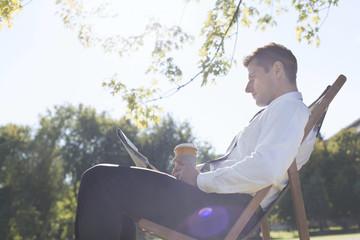 Polen, Warschau, Geschäftsmann bei einer Pause, Zeitung lesend