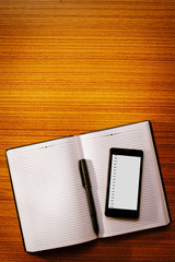 Mobile phone on an open blank notebook