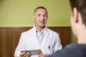 Arzt mit Tablet-PC im Gespräch mit Patienten