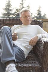 Portrait von reifem Mann, sitzt auf dem Balkon mit einer Tasse Kaffee