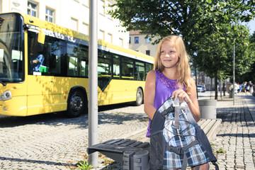 Mädchen mit Rucksack sitzt am Busbahnhof