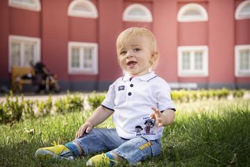 Deutschland, Oberhausen, blondes Baby sitzt im Park von Schloss Oberhausen