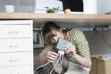Junge Frau hockend unter einem Schreibtisch, ein Modem in einem Büro