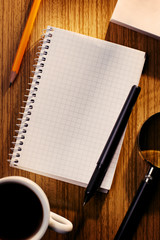 Grid Notebook and Cup of Coffee on Desk