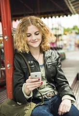 Teenager-Mädchen mit Smartphone auf Kirmes