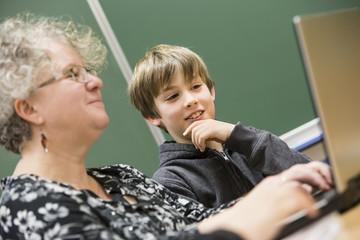 Portrait einer Lehrerin mit Schülern mit Laptop vor einer Tafel
