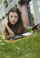 Junge Frau mit Tablet-PC in der Wiese