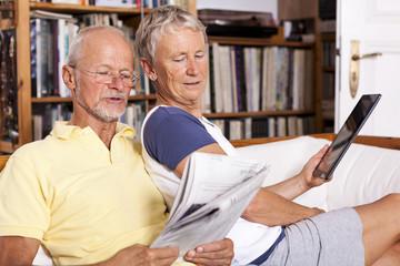 Senioren sitzen auf der Couch mit Tablet-PC und Zeitung
