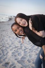 Deutschland, Rügen, zwei junge Freundinnen am Strand, Huckepack nehmen