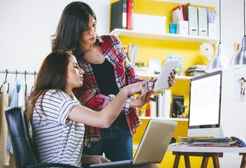 Zwei weibliche Mode-Blogger mit Computer, Laptop und Tablet-PC im Büro