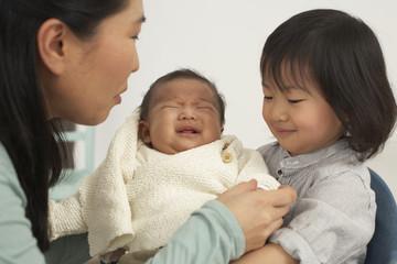 Asiatische Mutter mit Kleinkind und Baby