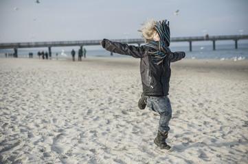 Deutschland, Mecklenburg-Vorpommern, Rügen, kleiner Junge läuft am Strand im Winter