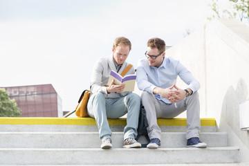 Zwei junge Männer sitzen auf Treppe
