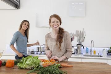 Zwei junge Freundinnen, die zusammen kochen