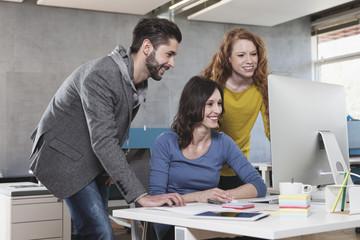 Blick auf Computer, drei Kollegen im Büro
