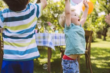 Kinder versuchen Seifenblasen im Garten zu fangen