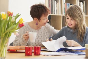 Deutschland, Berlin, Mutter und Tochter sprechen über Hausaufgaben