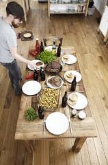 Man serviert Teller auf Holztisch