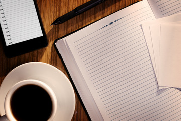 Open notebook with coffee alongside a phone