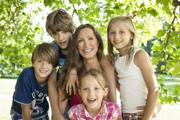 Deutschland, Berlin, Mutter im Park mit vier Kindern