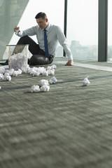 Geschäftsmann sitzt auf Büroetage, von zerknittertem Papier umgeben