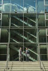 Zwei Geschäftsleute sprechen außerhalb Bürogebäude